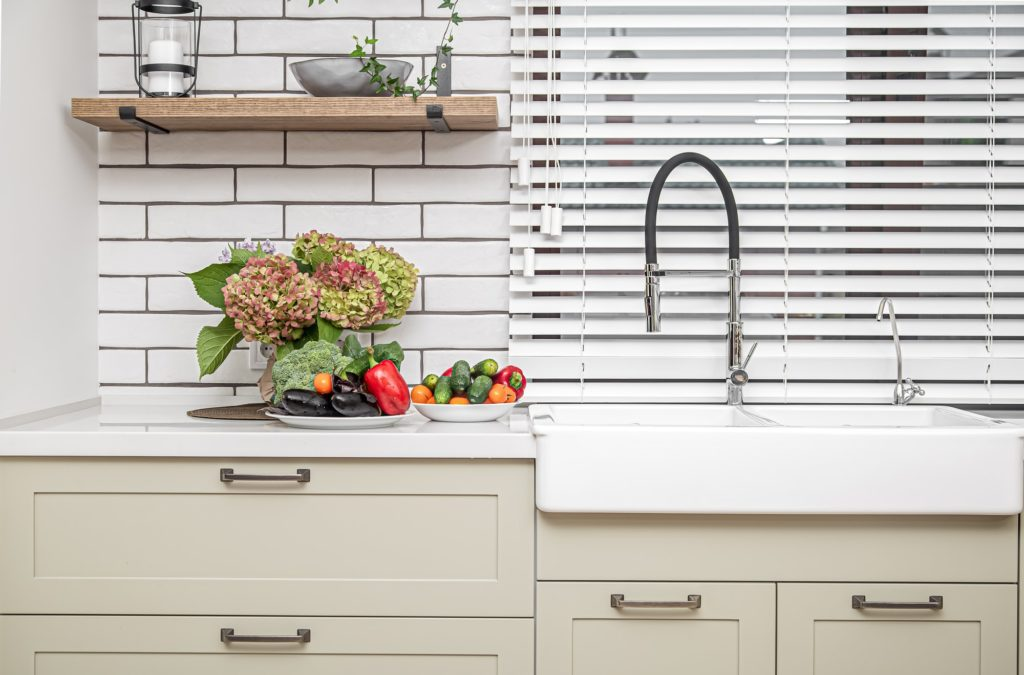 Kitchen interior near the wash basin with white cabinets in a minimal style.