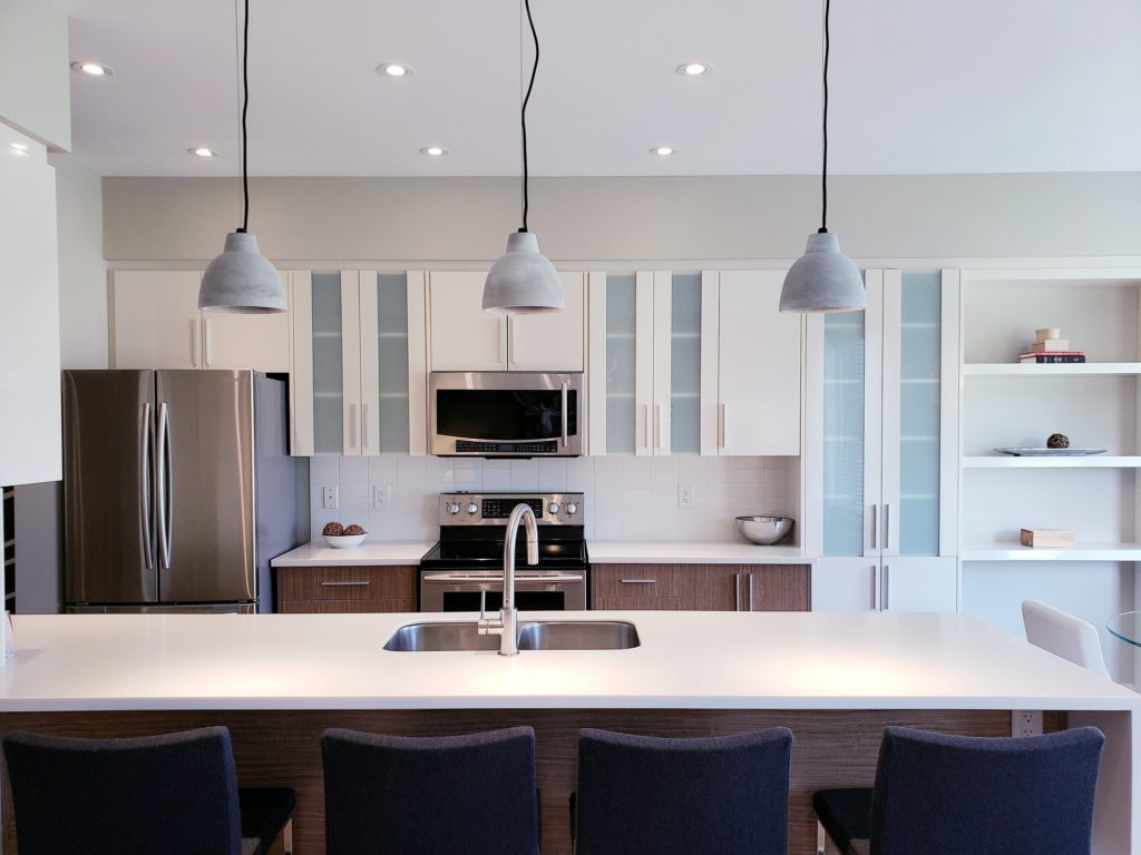 Modern design kitchen cabinets in white and tinted glass, quartz countertop, lights fixtures